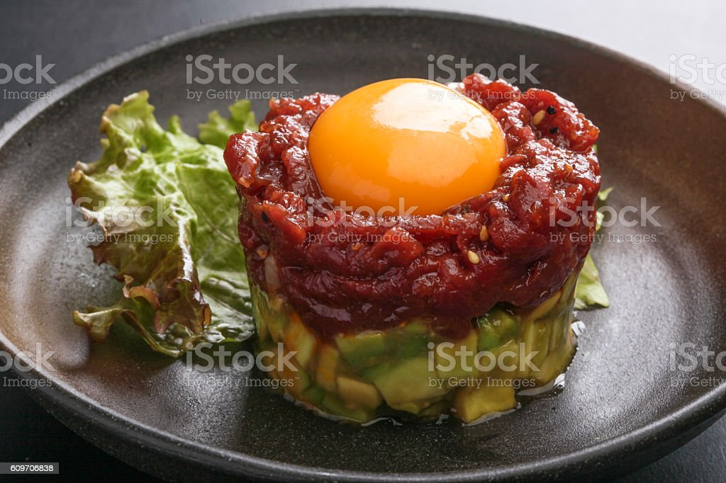 Avocado tartare stab Sakura beef meat with red egg and stock photo