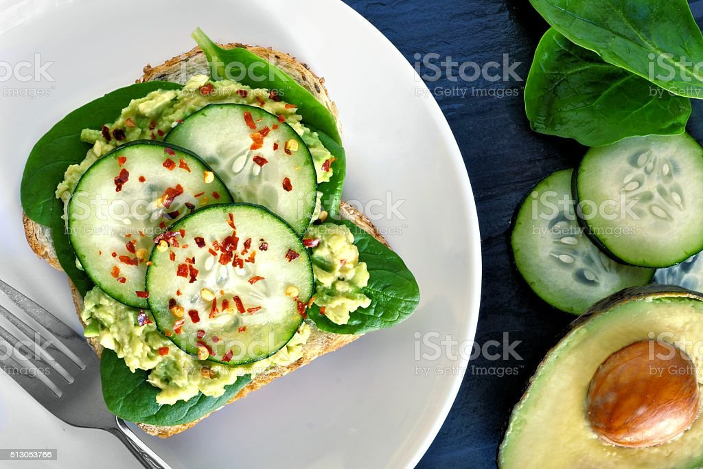 Avocado toast with cucumber and spinach on white plate stock photo