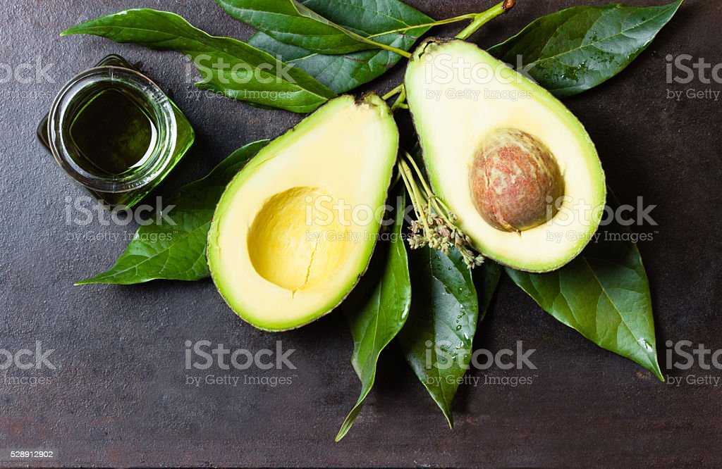 Avocado with leaves and jar of green oil. black background stock photo