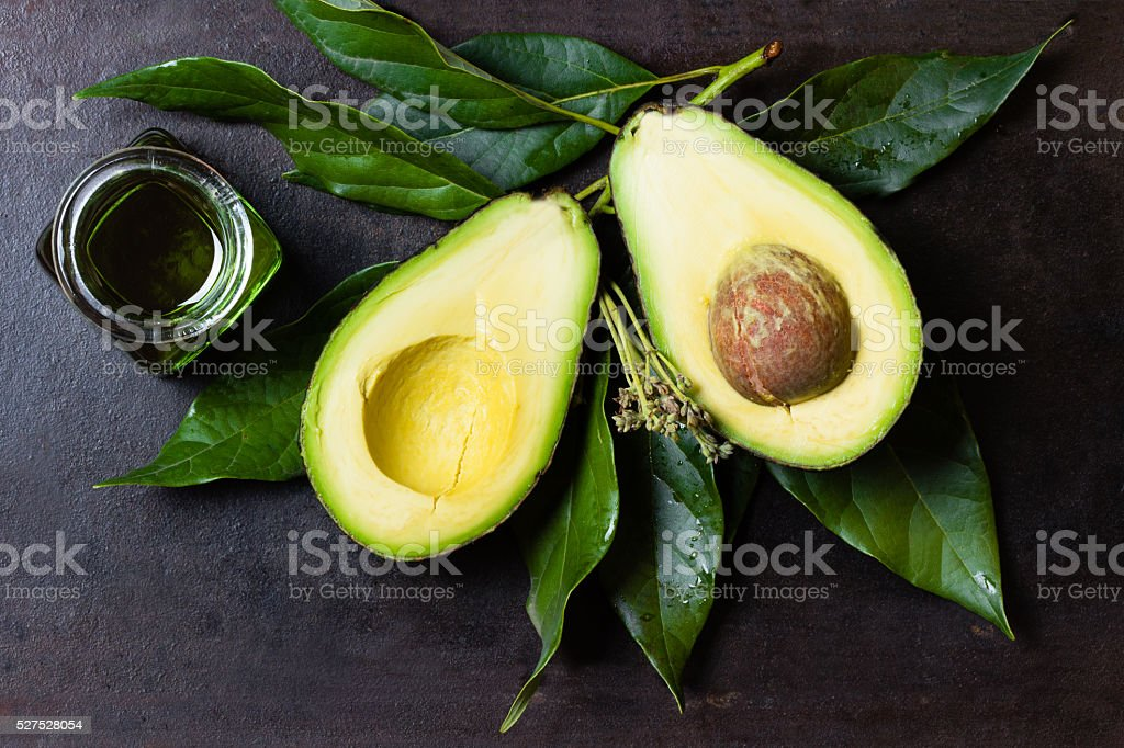 Avocado with leaves and jar of oil on black background stock photo