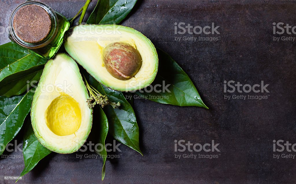 Avocado with leaves on black background. top view stock photo
