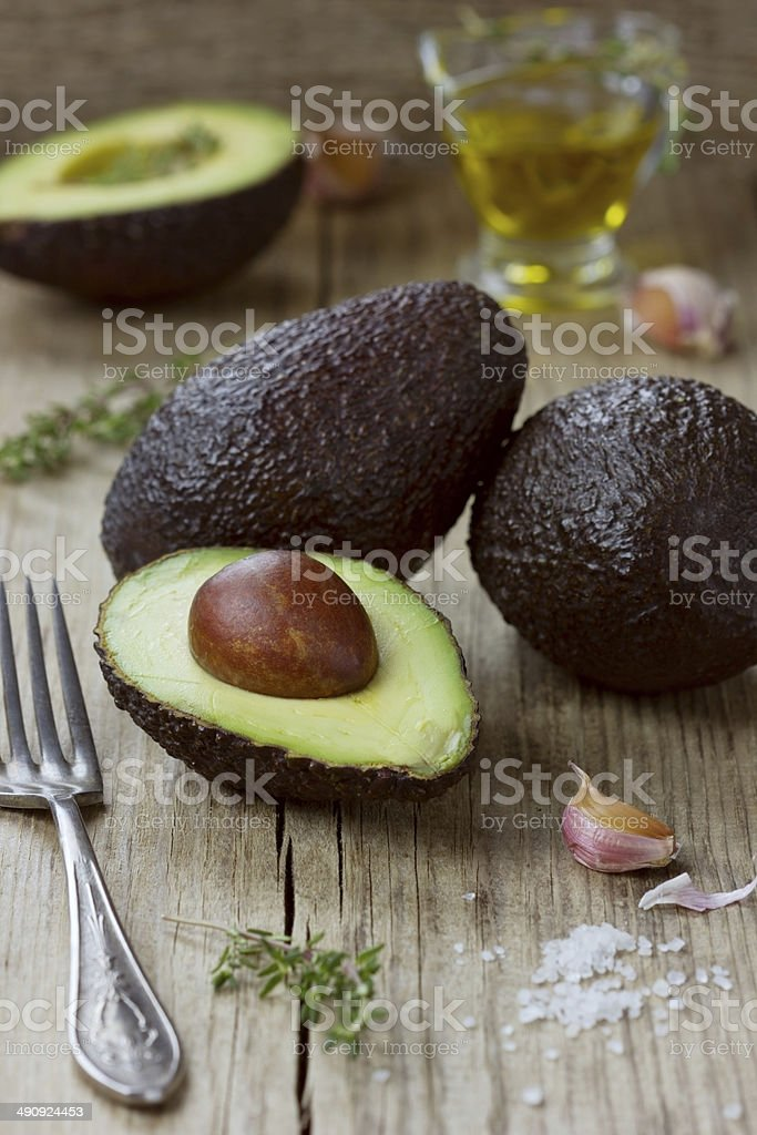 Avocado with olive oil, herb thyme and garlic stock photo