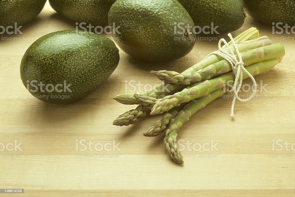 Avocados and asparagus on butcher block royalty-free stock photo