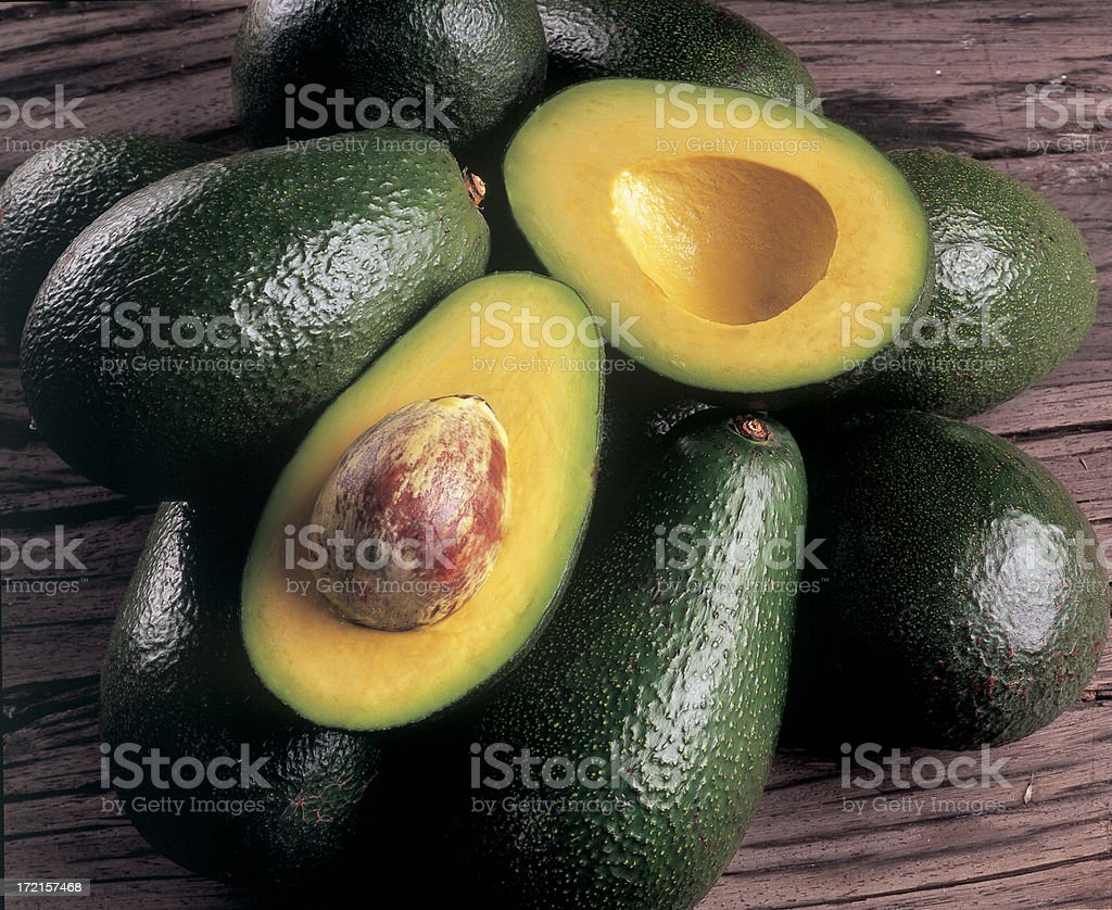 Avocados piled on top of each other with one cut open stock photo