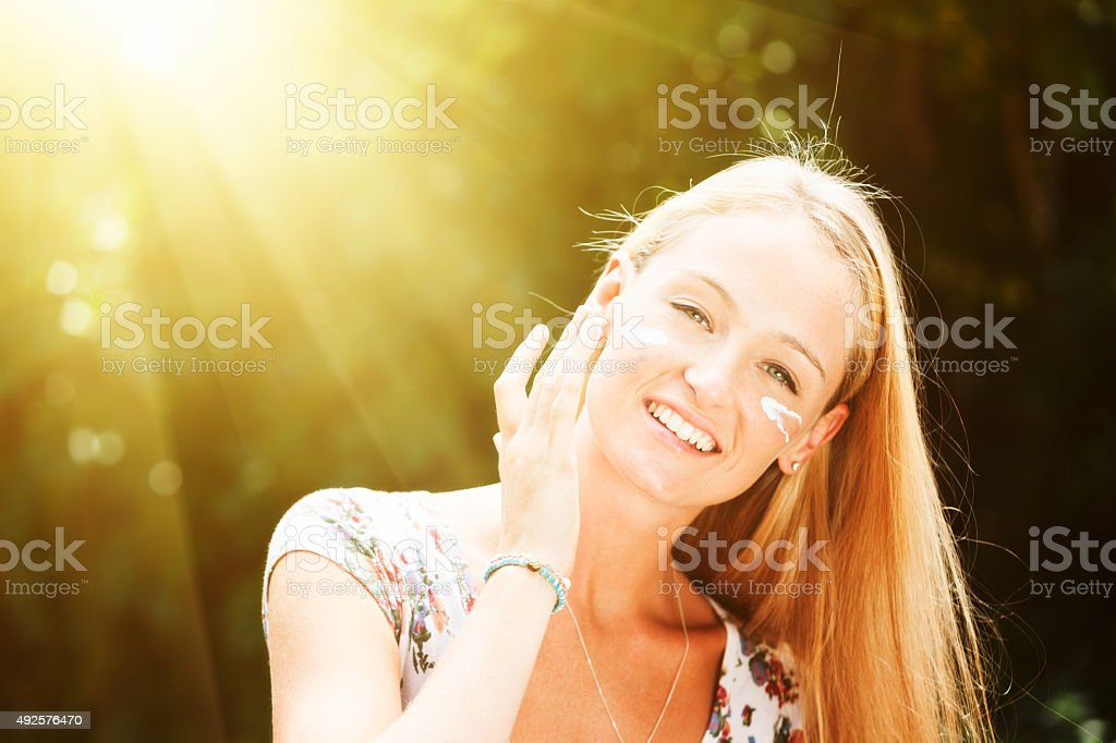 Avoiding skin cancer and wrinkles, beautiful blonde applies sunscreen stock photo