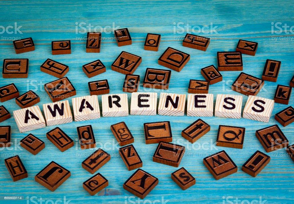 awareness word written on wood block. Wooden alphabet on a blue background stock photo