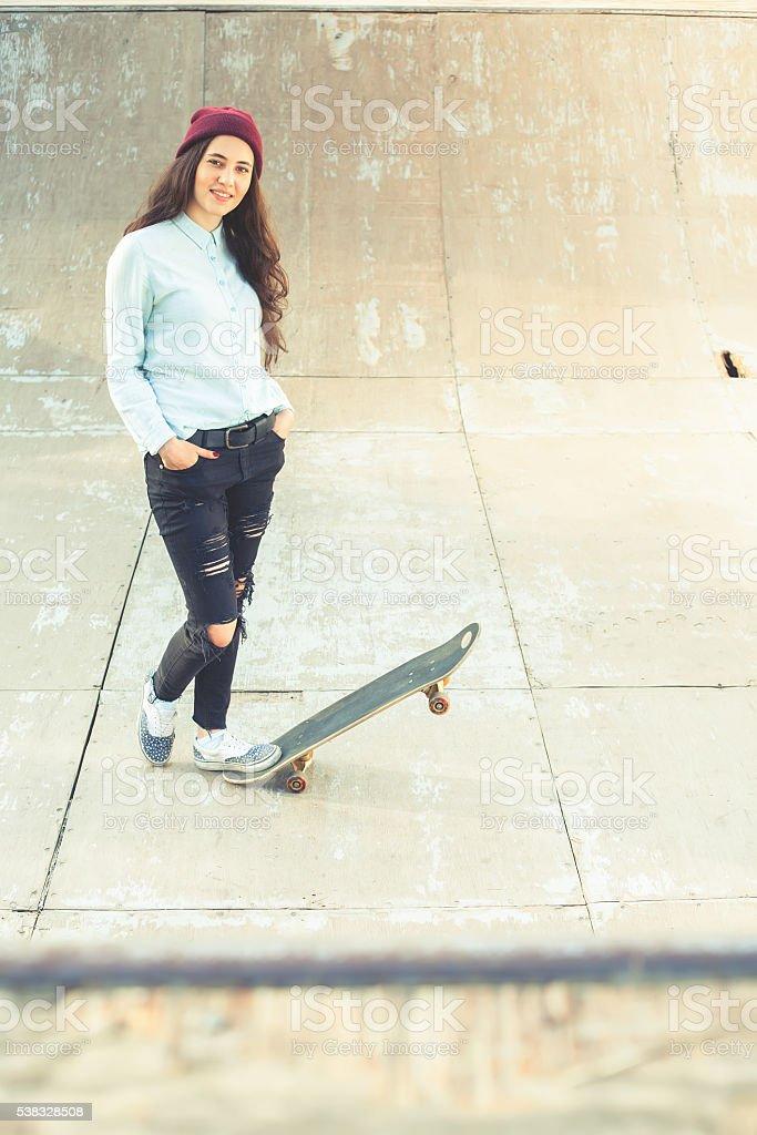 Awesome skateboarder girl with skateboard outdoor at skatepark stock photo