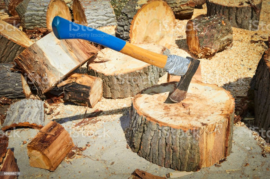 Ax stuck in a log of wood on a background of chopped wood stock photo