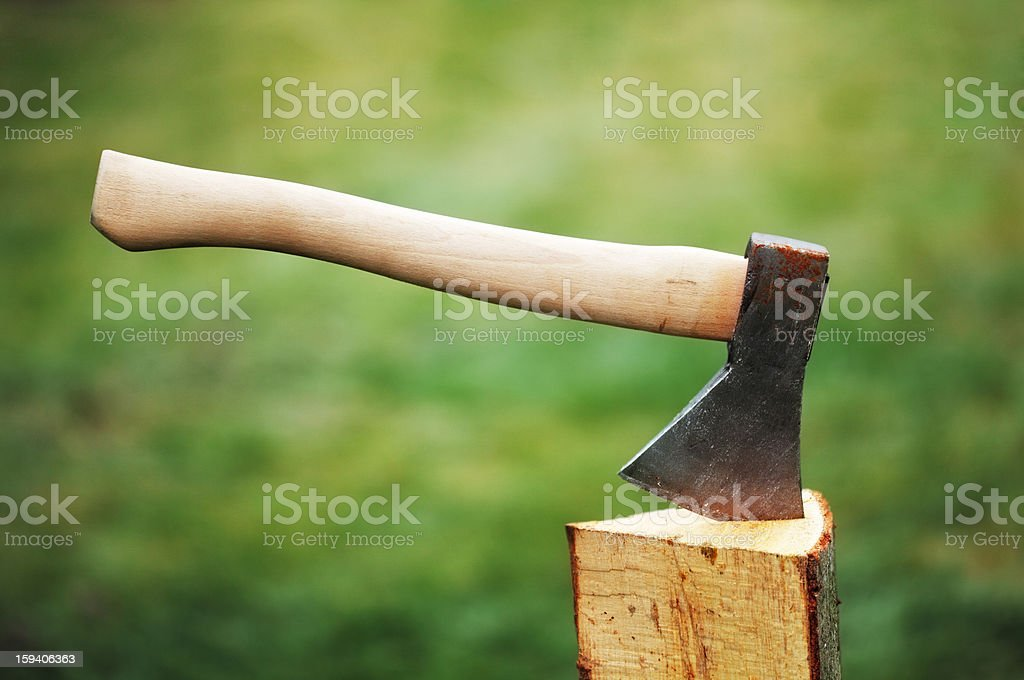 Axe in a log on the background of green grass royalty-free stock photo