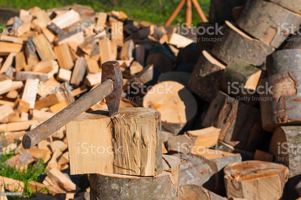 Axe in Chopping Block and Firewood. Ax pile of chopped stock photo