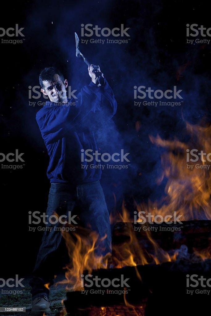 Axe wielding maniac by a fire stock photo