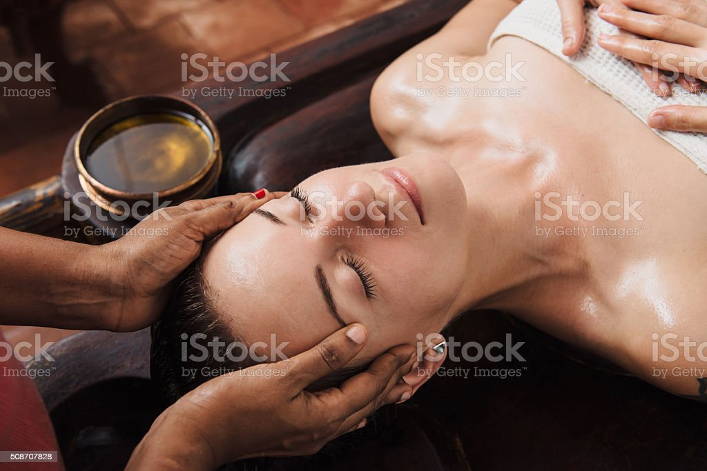 Ayurvedic face massage with oil on the wooden table stock photo