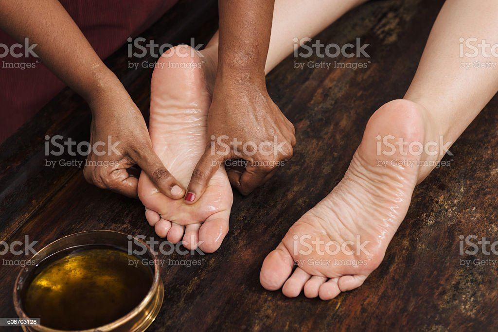 Ayurvedic foot massage with oil on the wooden table stock photo