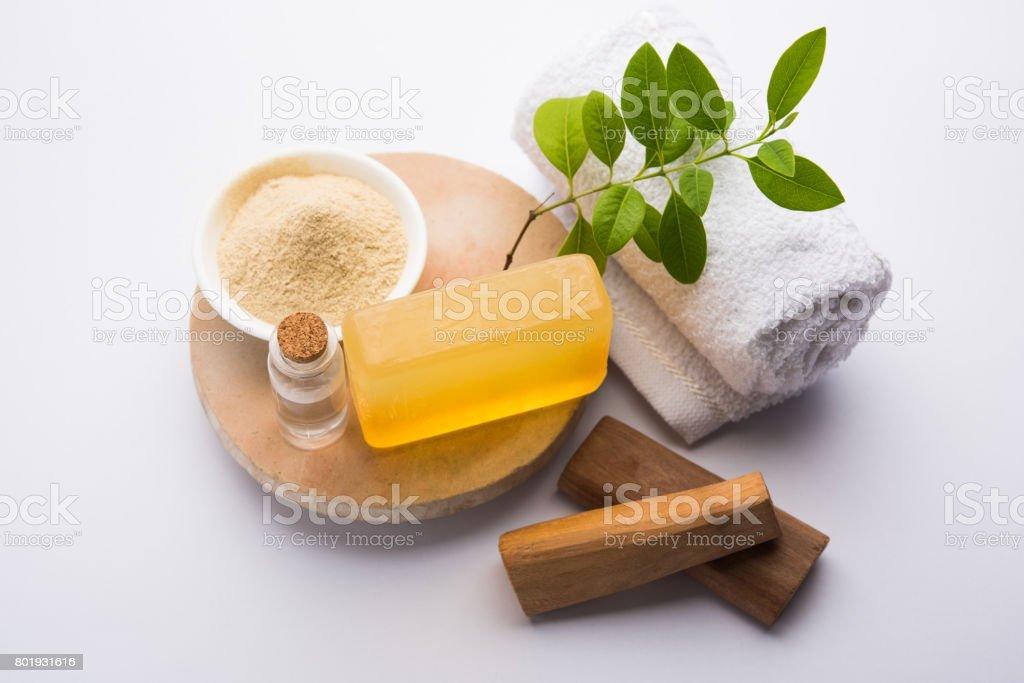 Ayurvedic handmade  Sandalwood both soap or chandan sabun with sandalwood sticks, ubtan or scrub or powder, oil and white towel, selective focus stock photo