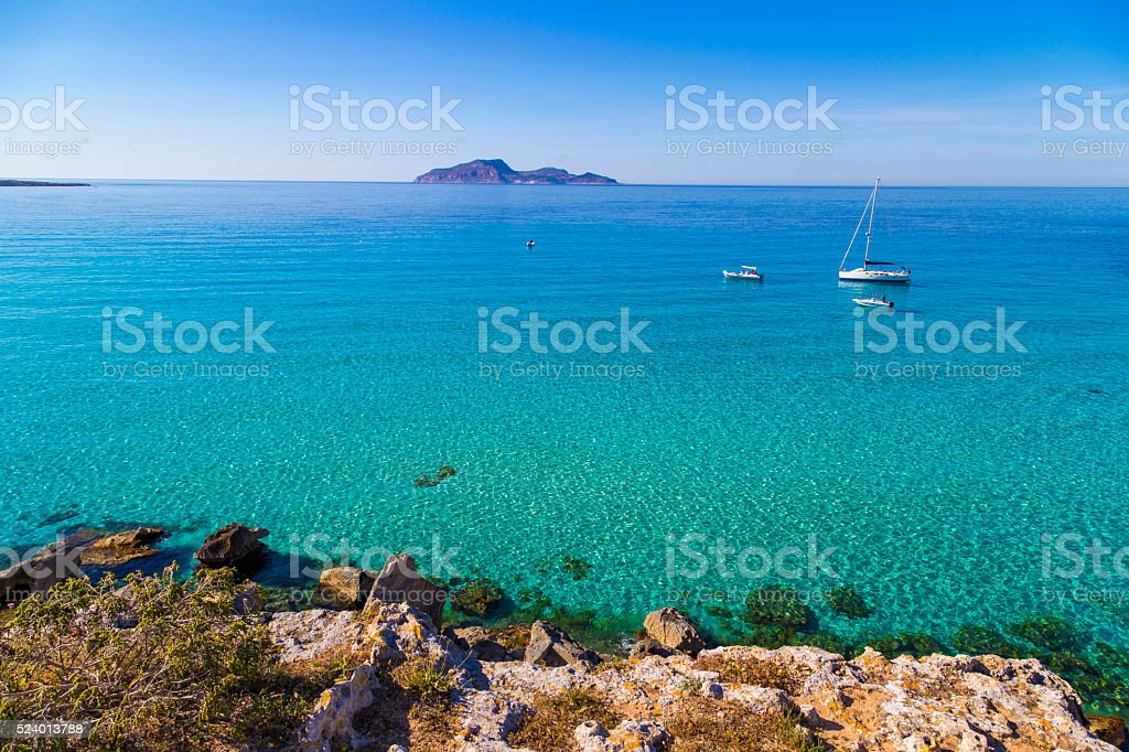 Azure lagoon called Cala Rossa with yachts moored stock photo