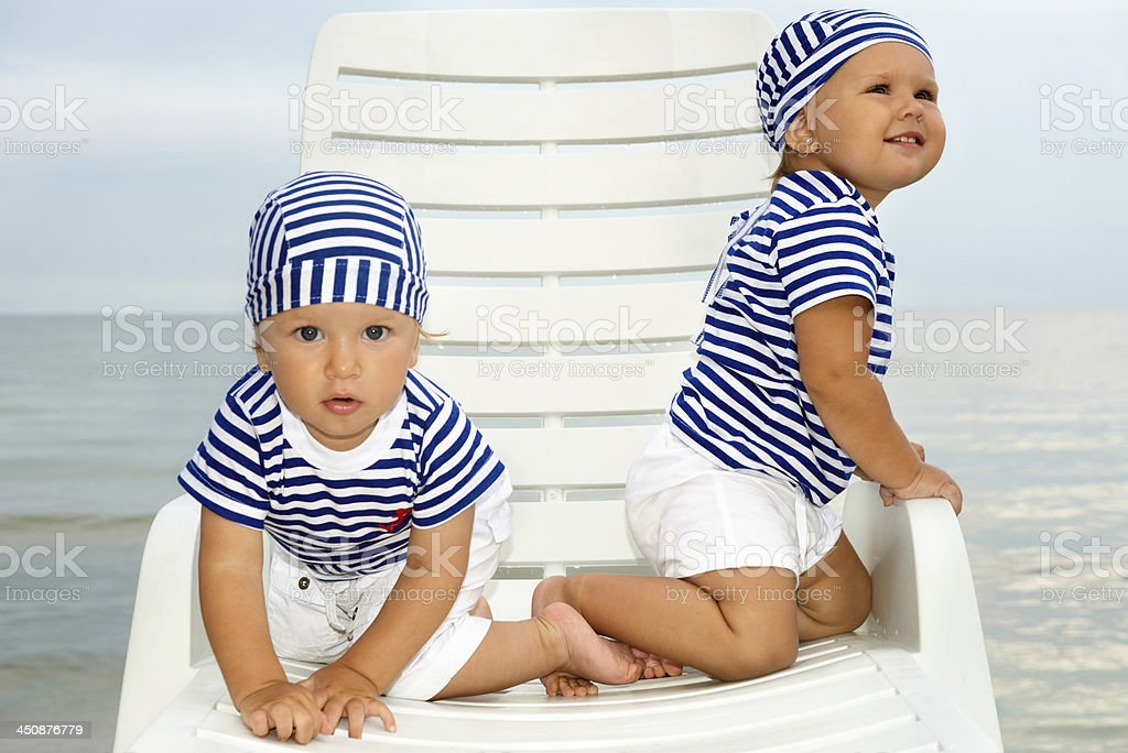Babies play on white lounge chair royalty-free stock photo