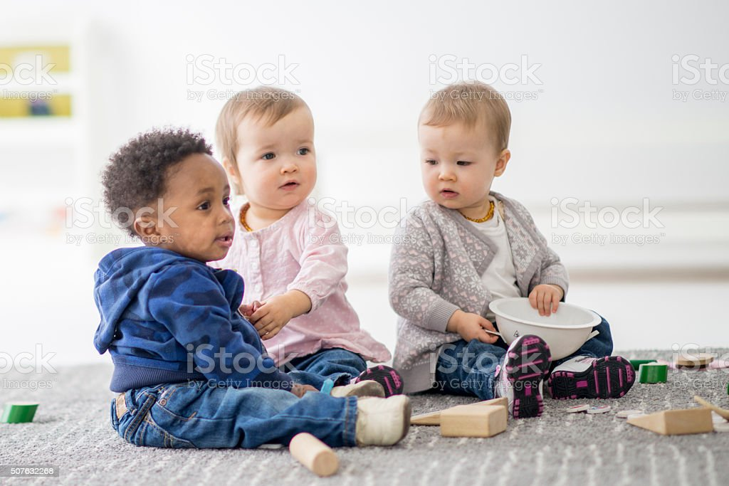 Babies playing together in preschool. stock photo