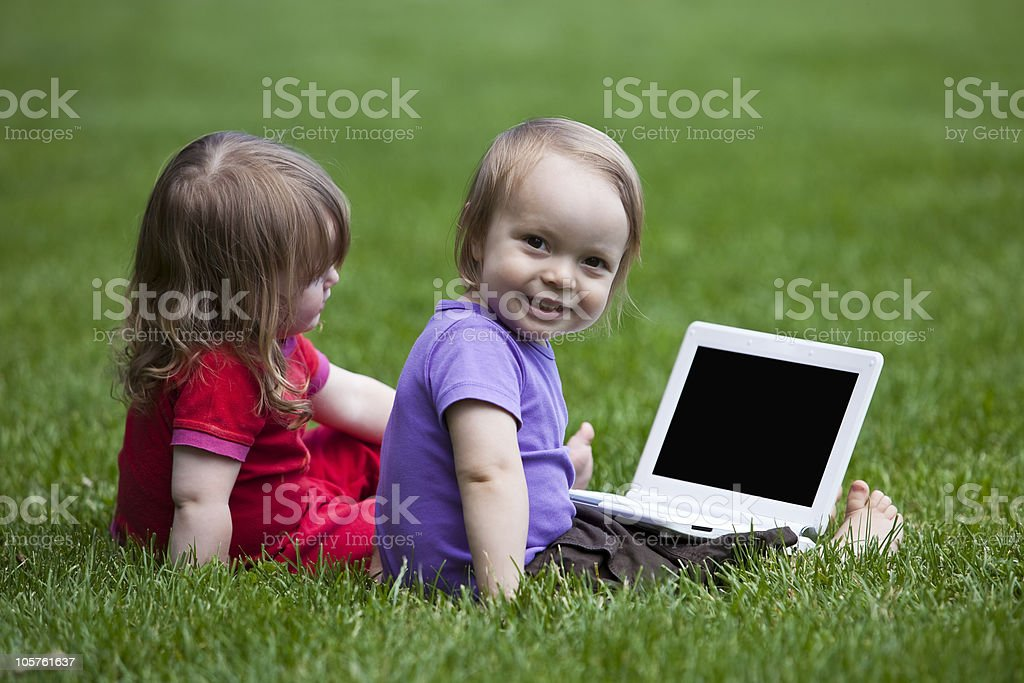 Babies with Notebook sitting on meadow royalty-free stock photo