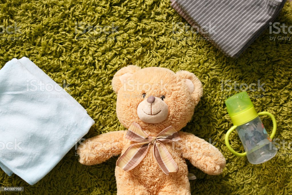 Baby accessories and toy on the green carpet stock photo