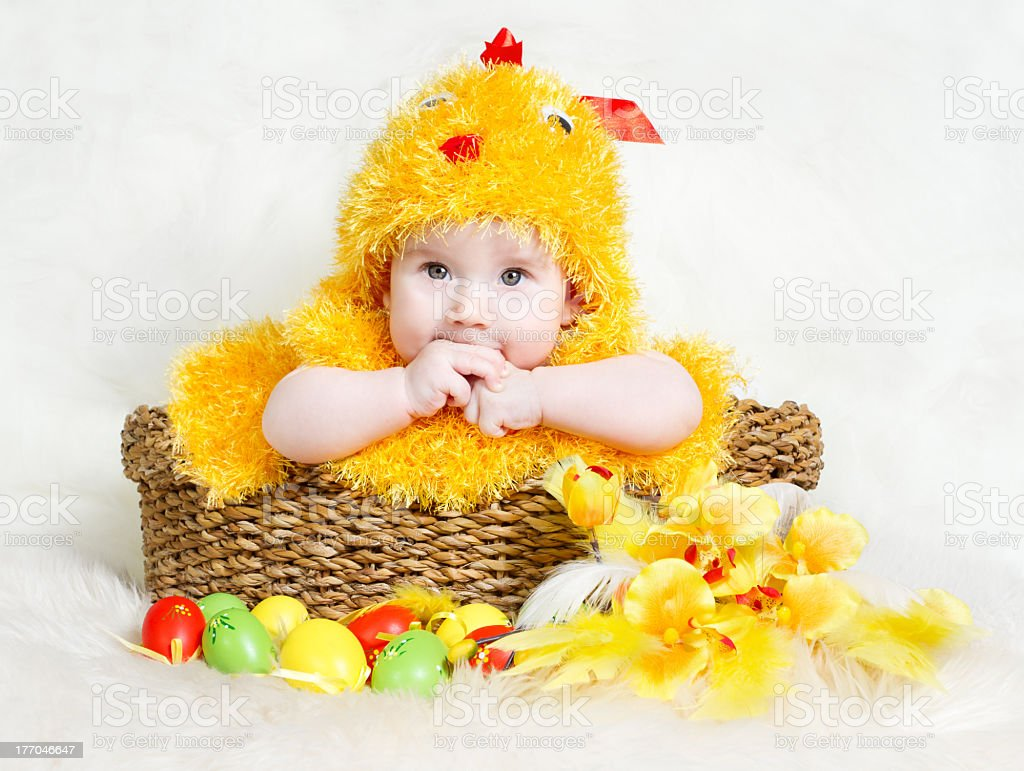 Baby and Easter basket with eggs in chicken costume stock photo