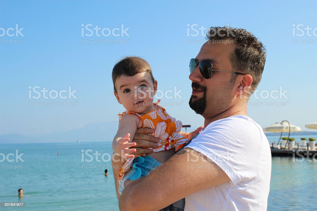 baby and father on the beach stock photo