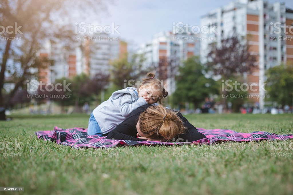 baby and her mother outside sleeping stock photo