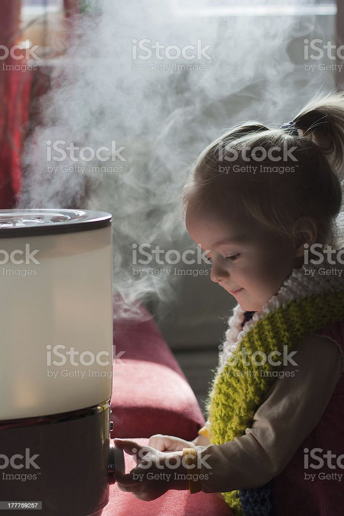 Baby and humidifier stock photo