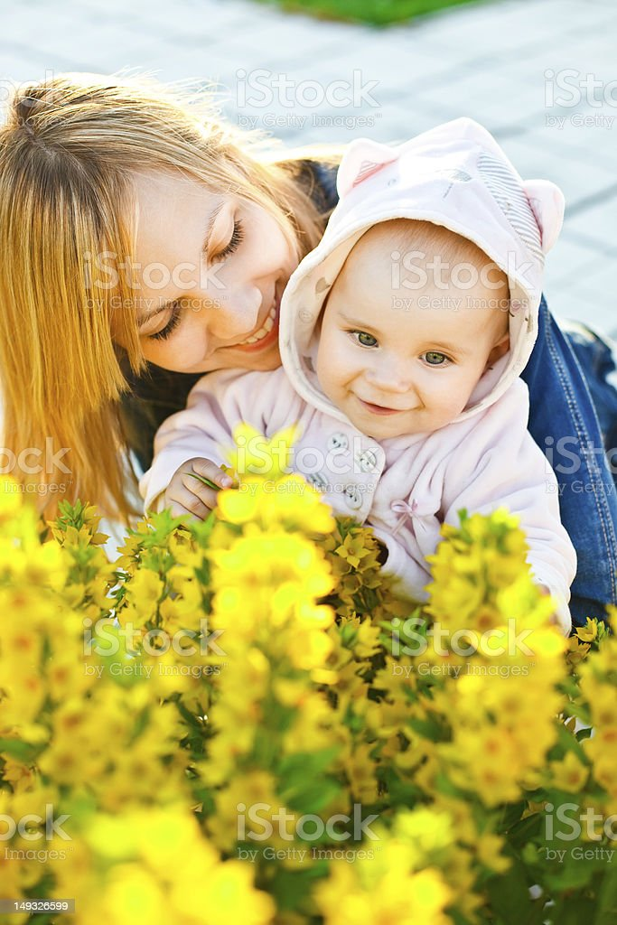 Baby and mother looking on flowers royalty-free stock photo