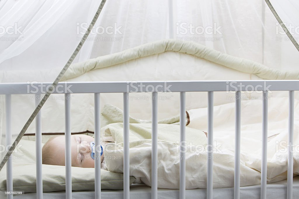 Baby asleep in bed stock photo