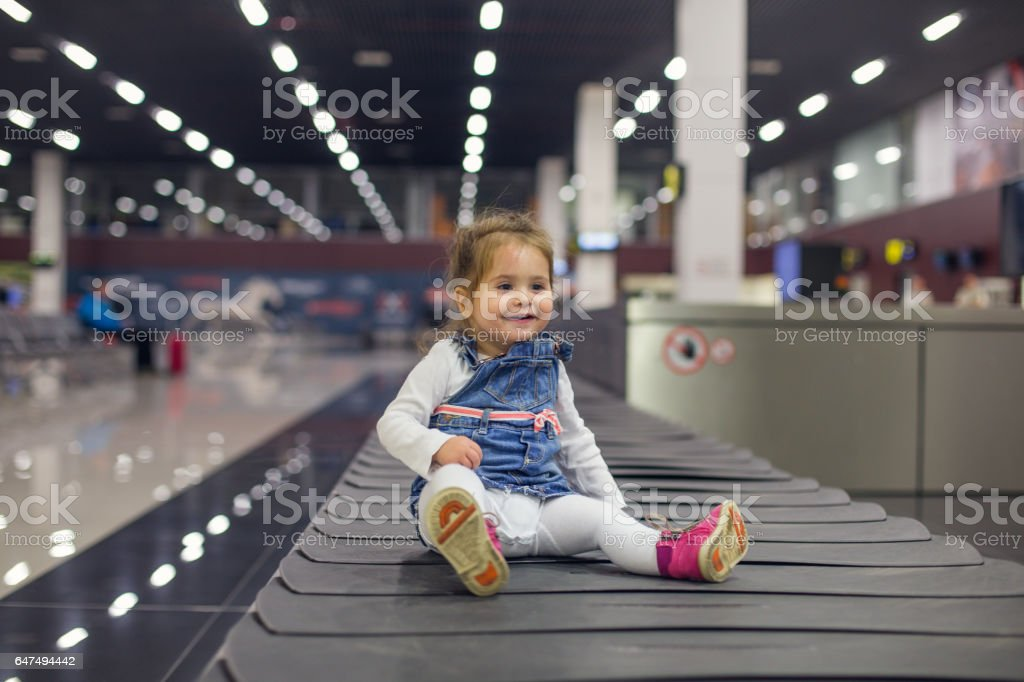 Baby at airport, smiling on carousel belt and havin fun stock photo
