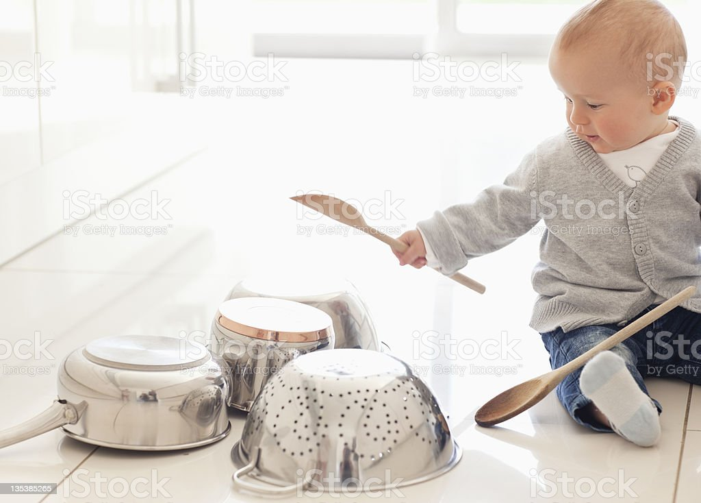 Baby banging on pots with wooden spoon royalty-free stock photo