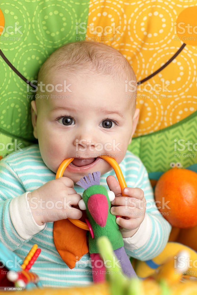 Baby biting rattle stock photo
