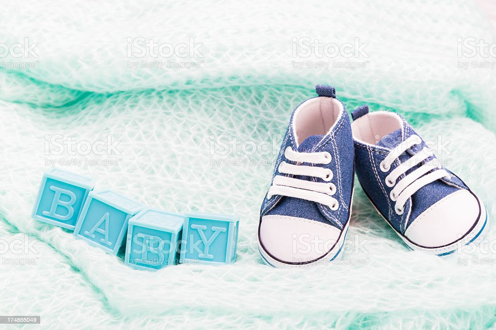 Baby blocks with shoes on blanket royalty-free stock photo