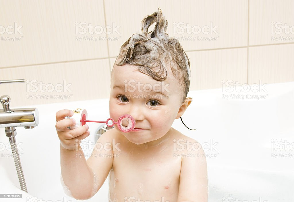 A baby blowing bubbles while taking a bath stock photo