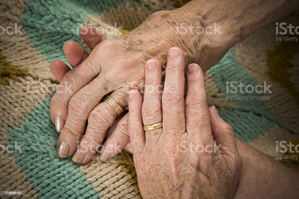baby boomer daughter holds her senior mother's hand stock photo