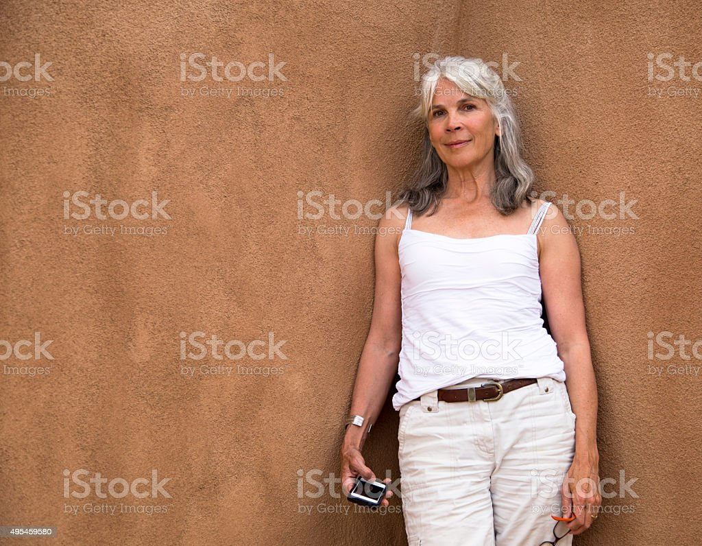 Baby boomer holding a cell phone and glasses stock photo