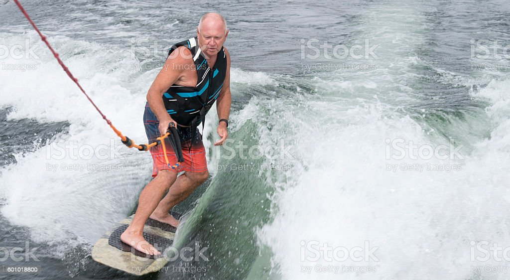 Baby boomer wakesurfing, wakeboarding stock photo