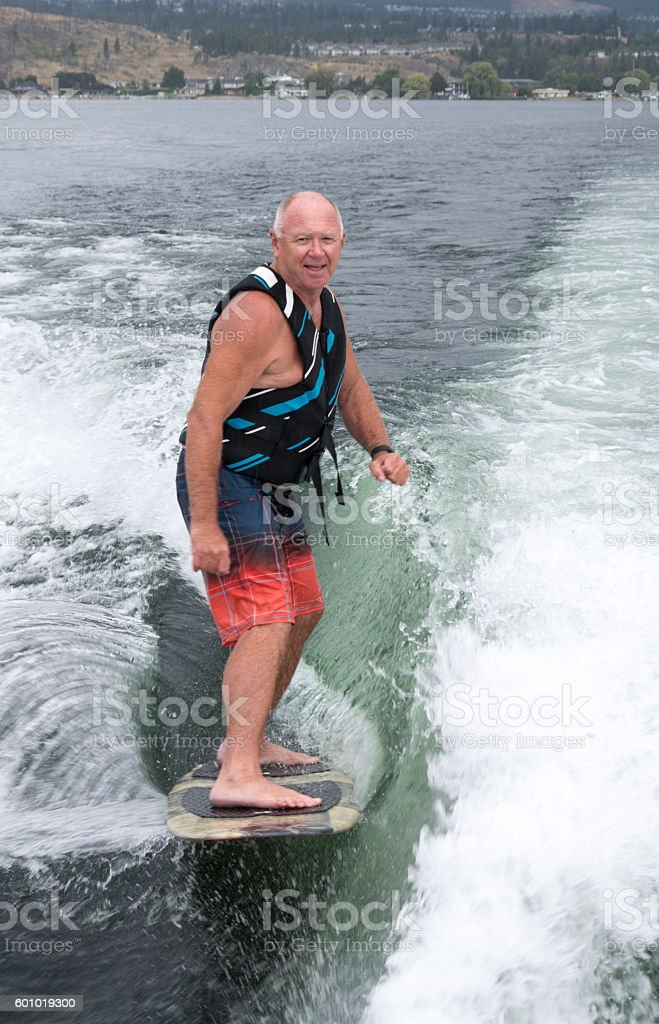 Baby boomer wakesurfing, wakeboarding, vertical stock photo