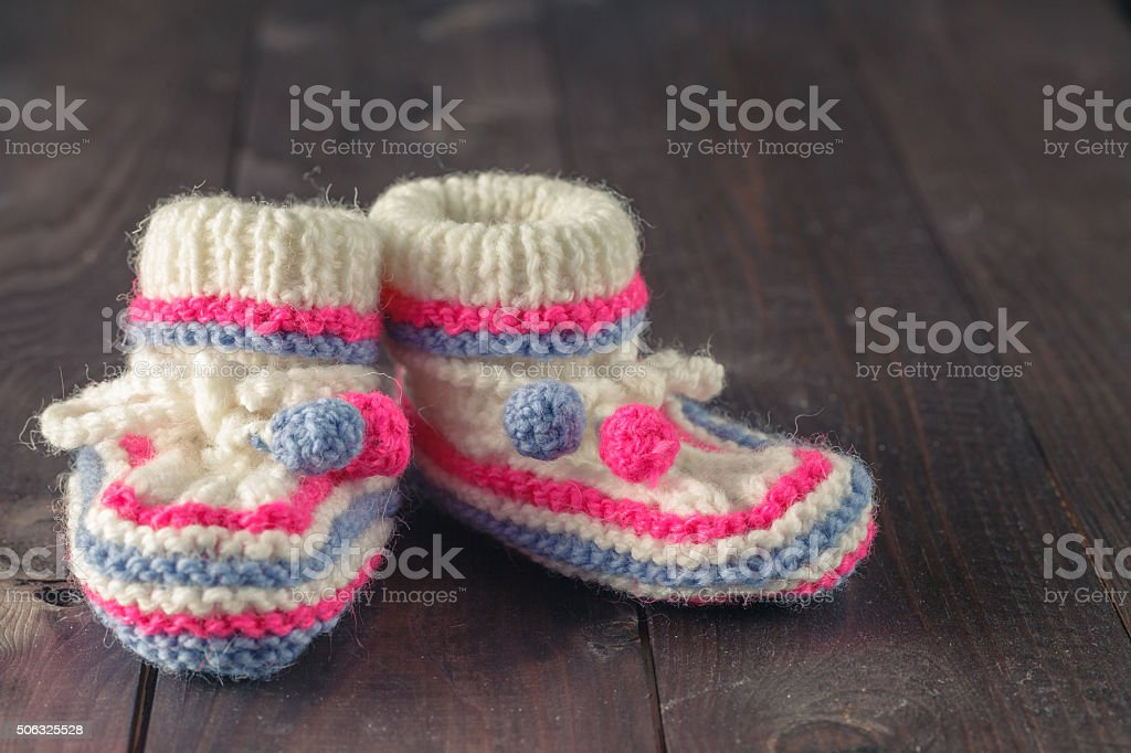 Baby booties on rustic wooden background stock photo