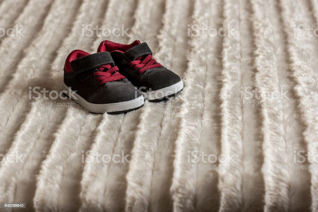 baby boots on the bed stock photo