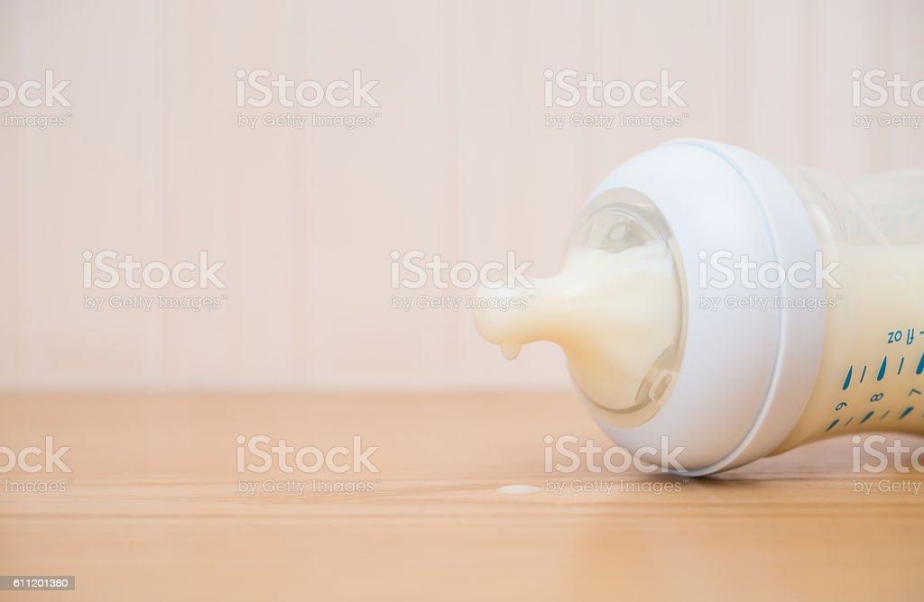 baby bottle and milk on a wood table close up stock photo