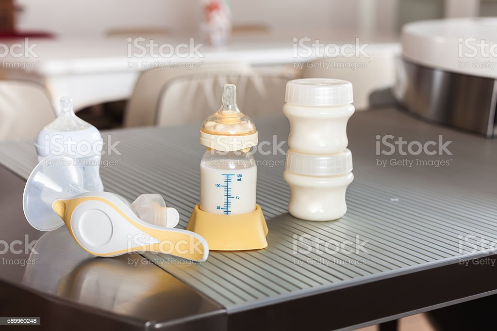 Baby bottle with milk and manual breast pump stock photo