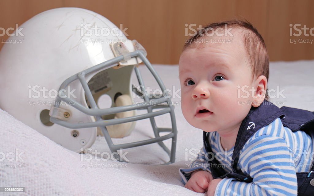 Baby boy and american football helmet. stock photo