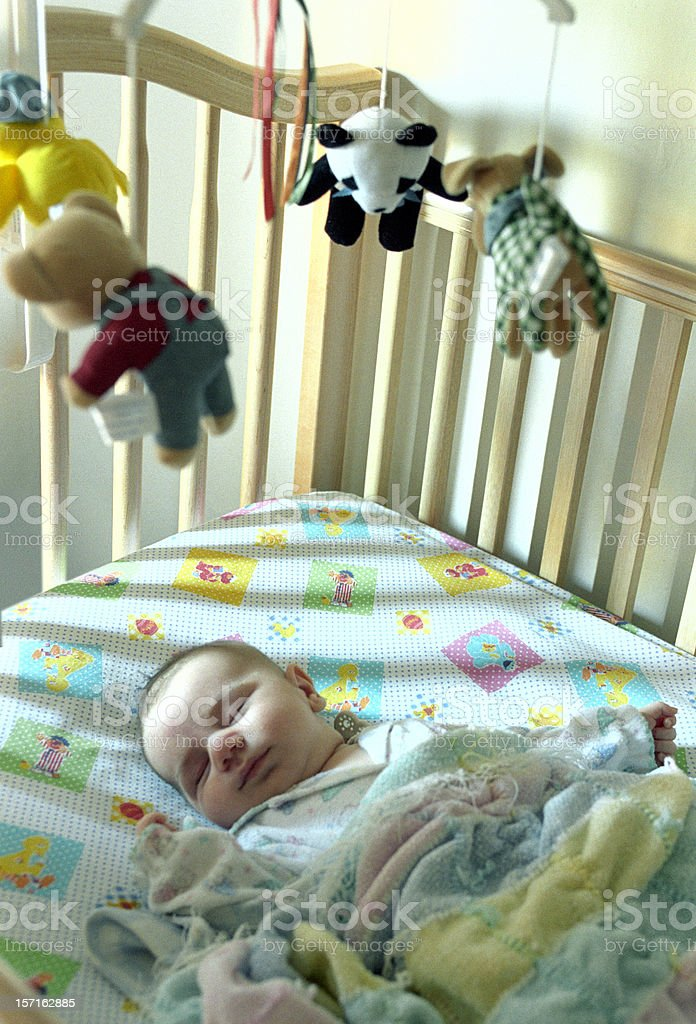 Baby boy asleep in his crib stock photo