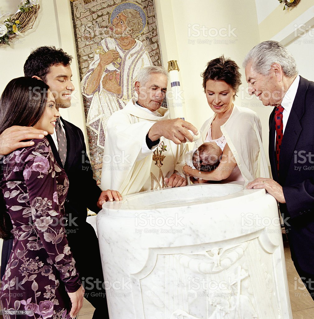 Baby boy (0-3 months) being baptised stock photo