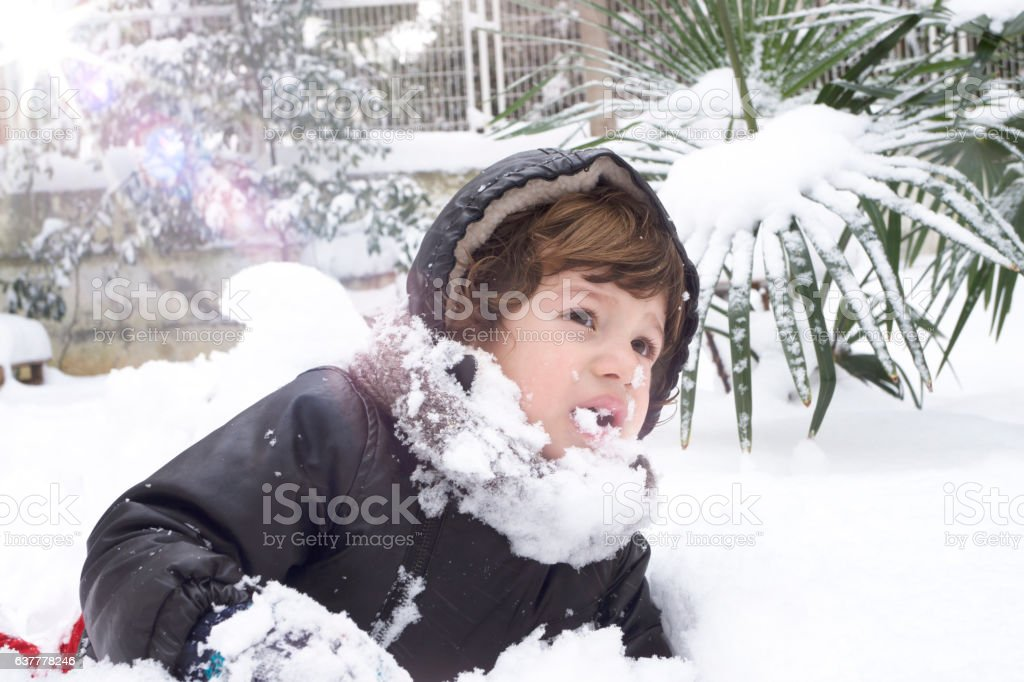 Baby boy catching snowflakes in winter park stock photo