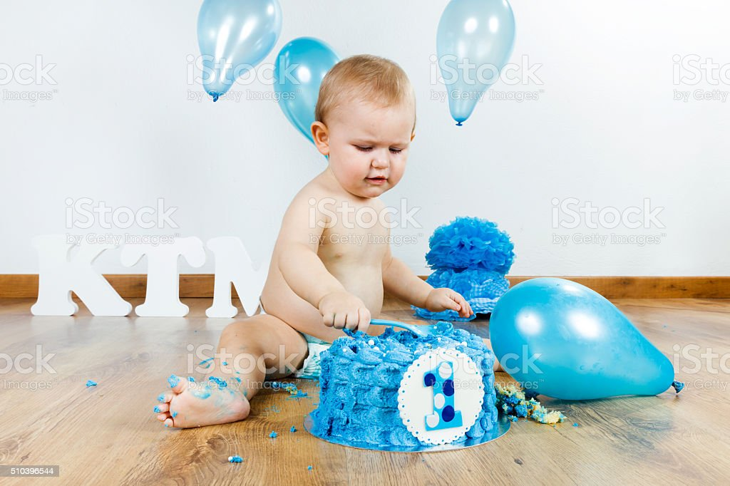Baby boy celebrating her first birthday with gourmet cake. stock photo