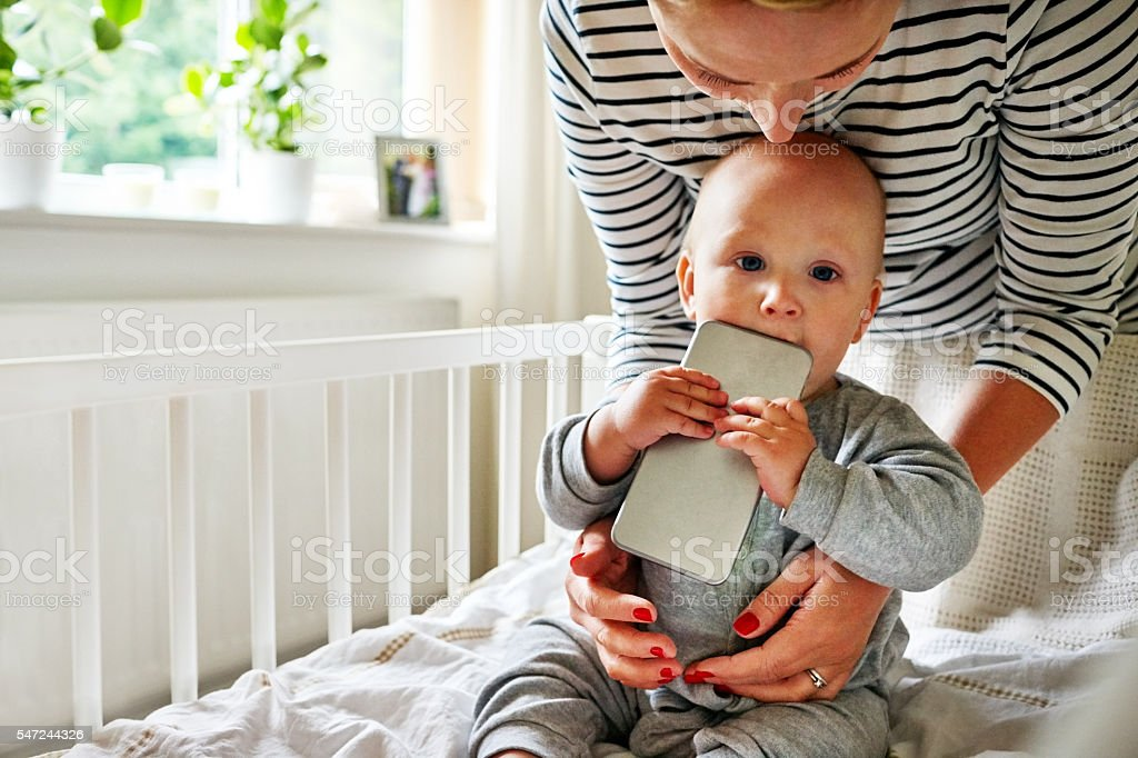 Baby boy chewing a cellphone in crib stock photo