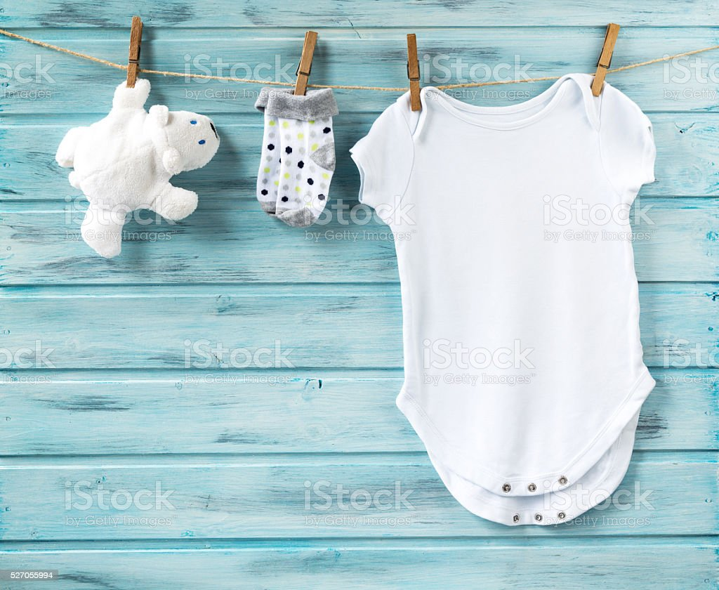 Baby boy clothes and white bear toy on a clothesline stock photo