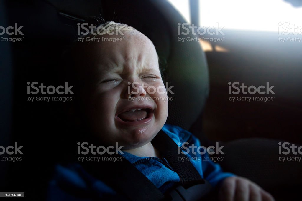 Baby boy crying in car seat stock photo